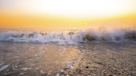 Amazing background from sea waves splashing beach sand at sunset Фото со стока