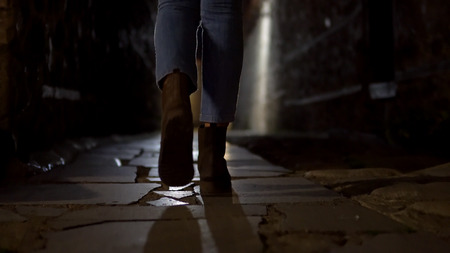 Woman feet in boot walking on stone pavement in old alley dark street