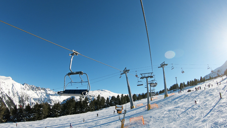 Mountains landscape pov with ski slopes and ski lifts on sunny day at mountain summit Todorka in Bansko world cup ski resort in Bulgaria
