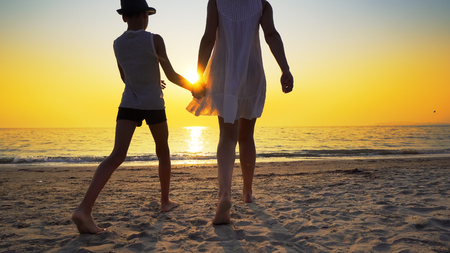 Mother with white dress and hat and son with hat standing barefoot on beach looking at the setting sun splashed by sea waves. Travel concept Фото со стока
