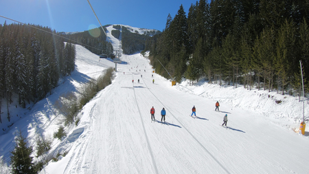 Aerial view of skiers and snowboarders on ski slope on sunny day