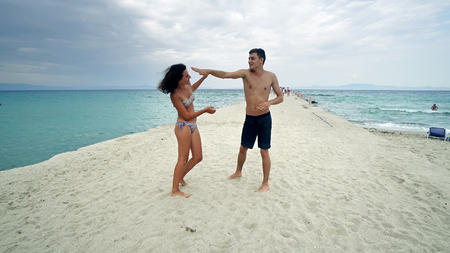 Young couple having fun fighting on the beach