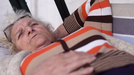 Talking elder woman lying in the garden porch swing bed, closeup