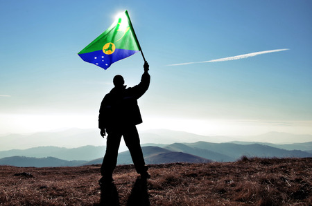 Successful silhouette man winner waving Christmas Island flag on top of the mountain peak Фото со стока