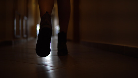 Dolly with low-section legs of silhouette woman running along corridor hallway in slow motion