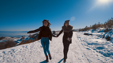 Two happy teen friends running on snow smiling, cinematic steadicam tracking shot Фото со стока