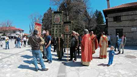 Bansko, Bulgaria - April 06, 2018: Easter parade ceremony on streets in Bansko, Bulgaria. Priests and people traditionally walk down the streets singing religious songs and giving Easter eggs to children