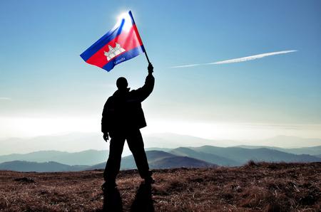 Successful silhouette man winner waving Cambodia flag on top of the mountain peak
