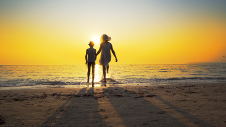 Mother with white dress and hat and son with hat standing barefoot on beach looking at the setting sun splashed by sea waves. Travel concept Imagens