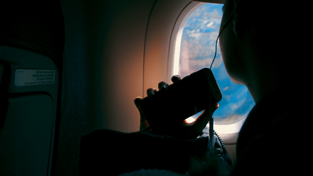 Happiness of asian girl with headphone listening music and taking pictures with smartphone and smiling looking on the airplane window Фото со стока