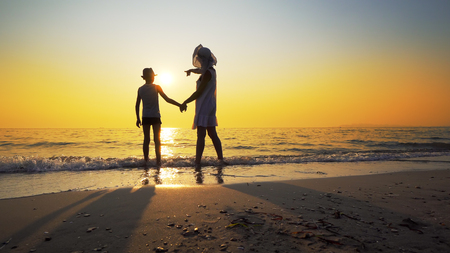 Family in love at summer sea sunset. Mother in white dress embrace little son with hat standing on empty beach