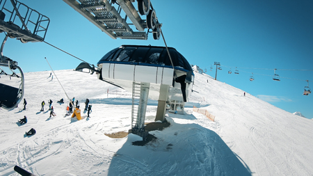 Ski lift with seats going over the mountain with view of people ski and snowboard on slope