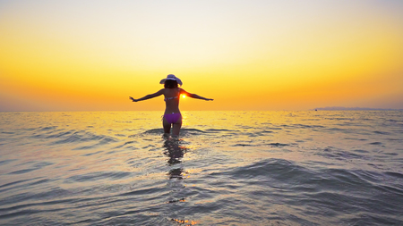 Sexy teen in bikini and hat go out of sea water at sunset, Summer vacation concept