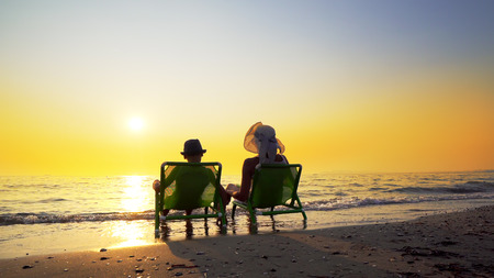 Happy family mother and son with hats enjoy luxury sunset on the beach during summer vacation. Travel concept