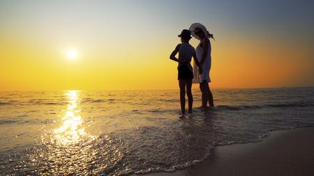 Family walk on beach to sea sunset and splash waves. Woman wear white dress and straw hat, boy has hat Standard-Bild