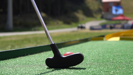 Nahaufnahme des Spielers spielen Minigolf mit rotem Ball