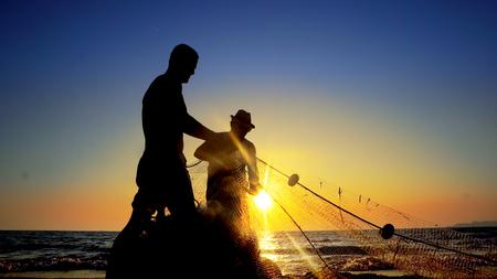 Fishermen working repairing fishing nets on ocean coast at sunset, cinematic shot Standard-Bild