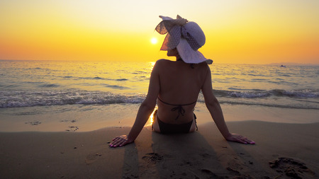 Hispanic woman with hat sitting on beach at sunset. Sea waves splash her body. Travel concept