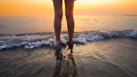 Woman feet splashed by sea waves on beach sunset. Calm serene relaxing scene of ocean water splashing on feet on beautiful beach Фото со стока
