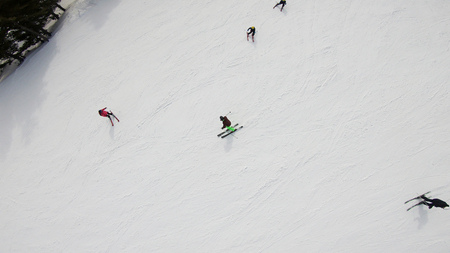 Aerial view of skier carving the mountain ski slope at high speed Фото со стока