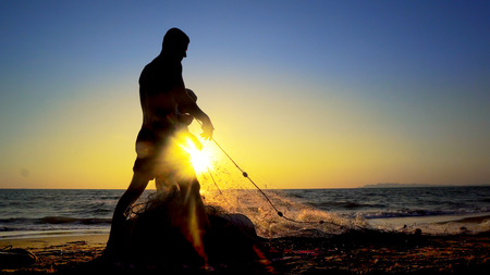 Silhouette Fishermen using fishing nets, fishing with nets in the morning sunrise, cinematic Фото со стока