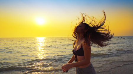 Beautiful model in swimsuit posing on the beach in sunset sunlight with long hair making forms