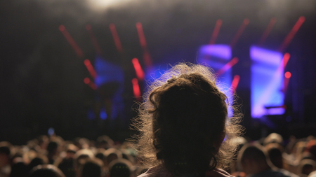A music fan girl on someones shoulders at a music festival.  Public concert, no ticketing event