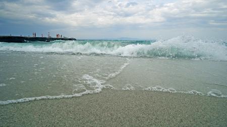 Splashing storm waves on a beach near pier.