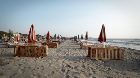 Empty beach in the seaside resort with folded sun loungers and umbrellas on a background of sunrise sky Фото со стока - 120639135