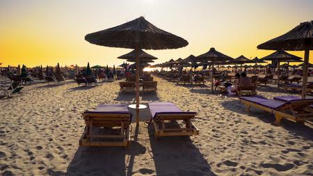 Luxury summer beach resort with straw umbrellas at sunset, cinematic steadicam shot