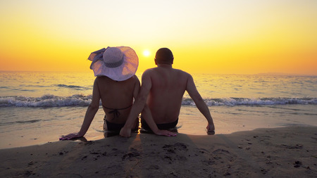 Couple relaxing on beach at tropical sunset, summer vacation concept Фото со стока - 120639224