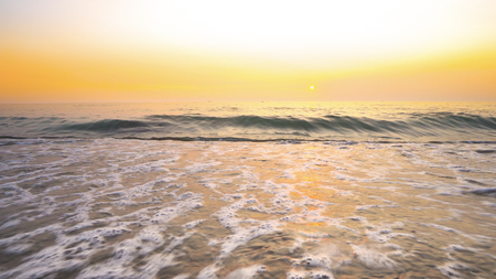 Sea waves crashing on beach at vibrant sunset at background Фото со стока - 120639232