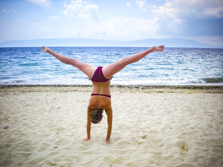 Cheerful caucasian young woman performing gymnastic working out in beach Фото со стока - 120639234