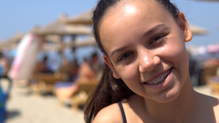 Beautiful happy teen girl with tooth braces smiling to camera sitting on beach during summer vacation