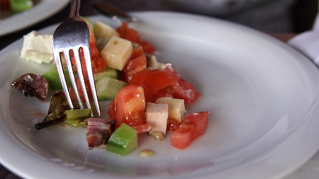 Eating a fresh mixed salad with tomato, cheese, ham, mushrooms, cinematic dof close up Фото со стока - 120639236