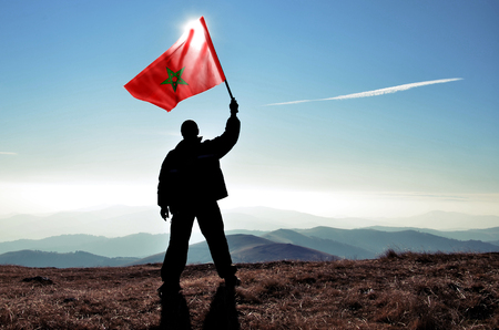 Successful silhouette man winner waving Morocco flag on top of the mountain peak Фото со стока - 120638836