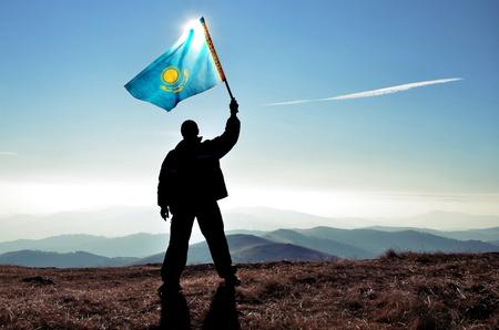 Successful silhouette man winner waving Kazakhstan flag on top of the mountain peak