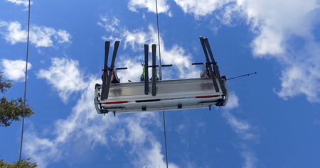 Ski lift carrying skiers on slope on top of mountains