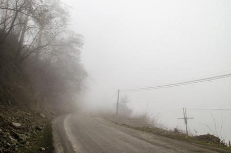 nowhere: Foggy Country Road. Fog creates a feel of emptiness as it leads to seemingly nowhere. Ilisu, Gakh, Azerbaijan Stock Photo