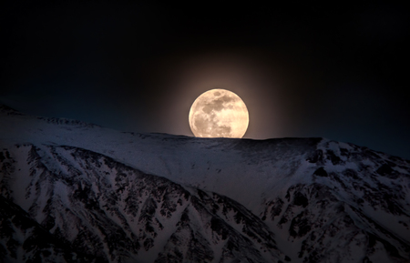 barstow: Super big Moon rises over snow capped mountains at twilight. Close up view of rising moon at night