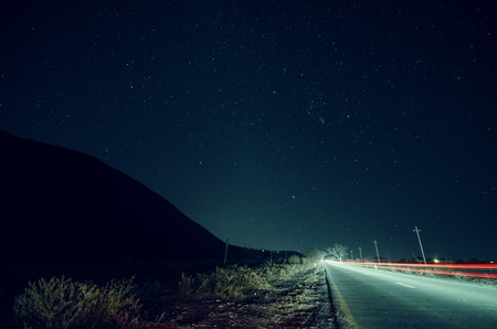 Beautiful night landscape of stars at sky and mountain silhouette near road with car trails. Road in the mountains under a starry gyres. Azerbaijan, Big Caucasus, Sheki Stock Photo