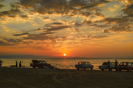 baku: Beautiful blazing sunset landscape at Caspian sea and orange sky above it with awesome sun golden reflection on calm waves as a background. Amazing sunset view on the beach. Azerbaijan Absheron, Baku