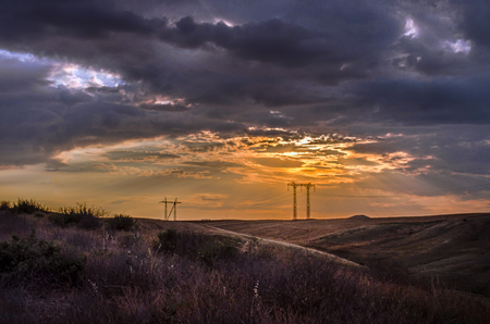 Road vanishing to the horizon under sun rays coming down trough the dramatic stormy clouds. Sunset at the mountain road. Azerbaijan, Stock Photo