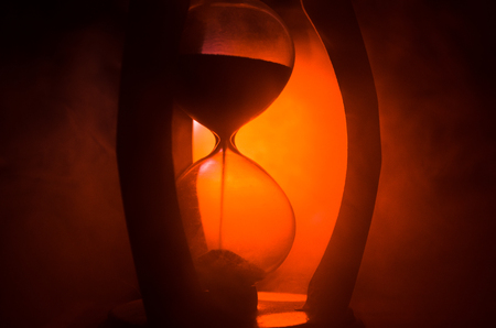 Time concept. Silhouette of Hourglass clock and smoke on dark background with hot yellow orange red blue cold back lighting, or symbols of time with copy space, sandglass or sand clock