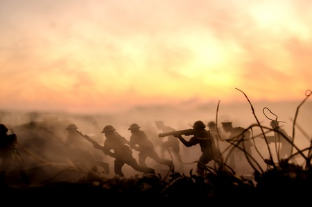 War Concept. Military silhouettes fighting scene on war fog sky background, World War Soldiers Silhouettes Below Cloudy Skyline At Dusk or Dawn. Attack scene