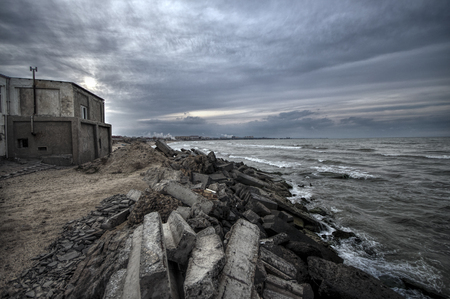 Beautiful surreal landscape of abandoned house and ladder on rocky seashore at sunset time. Cloudy weather. Caspian Sea, Azerbaijan, Novkhani