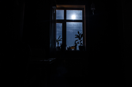 Night scene of moon seen through the window from dark room. Moonlight inside dark room