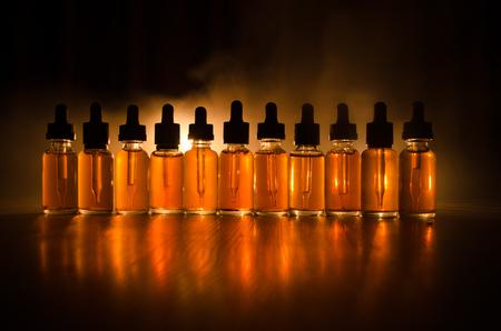 Vape concept. Smoke clouds and vape liquid bottles on dark background. Light effects. Useful as background or vape advertisement or vape background.