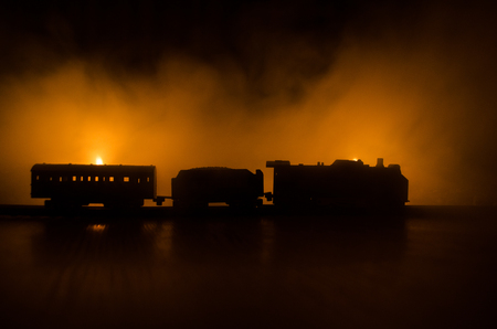 Train moving in fog. Ancient steam locomotive in night. Night train moving on railroad. orange fire background. Horror mystical scene
