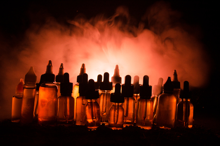 Vape concept. Smoke clouds and vape liquid bottles on dark background. Light effects. Useful as background or vape advertisement or vape background.